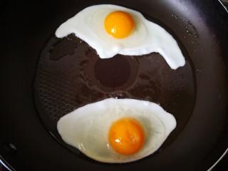 平菇鸡蛋汤,平底锅放油烧热,磕入两个鸡蛋