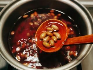 花生红枣汤,小火慢煮,汤水已经变成红色花生煮至体积增大。