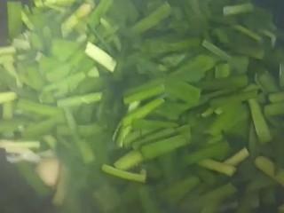 韭菜炒鱿鱼,倒入韭菜。