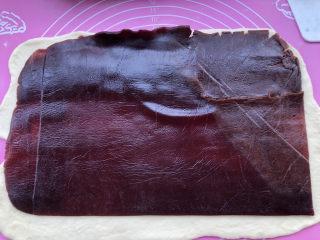 豆沙千层面包,撕开保鲜袋把豆沙馅叠压在面皮上。