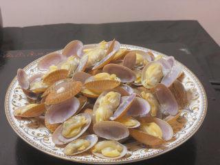 葱油花蛤,将煮开的花蛤盛到盘子里