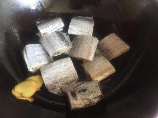 红烧带鱼,将生姜片放一边,下入带鱼稍微煎一下