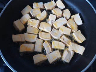 韭黄炒豆腐,热锅倒入油 ,放入豆腐两面煎至微黄