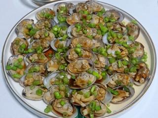 葱油花蛤,把切好的小葱末均匀的撒在花蛤肉上