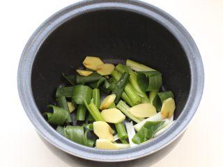 酱香排骨,将小葱切成段、姜切片,放进电饭煲内胆底部。