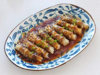肥牛金针菇卷,取出蒸好的肥牛金针菇卷,淋上调味汁再撒葱花即可。