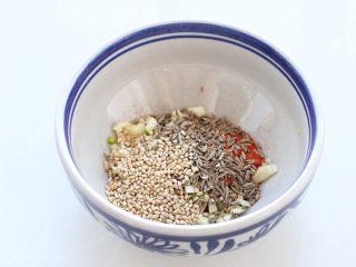 干煸豆腐,小碗中放入蒜末、孜然粒、白芝麻和辣椒粉,具体用量可根据个人口味添加。