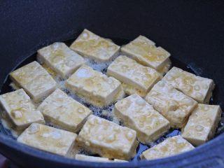 干煸豆腐,平底锅中倒适量食用油烧热,依次放入豆腐块开小火煎制。