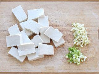 干煸豆腐,将老豆腐切成大小适中的块状,准备蒜末和葱花。