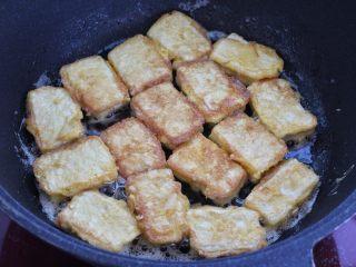 干煸豆腐,一面煎至定型焦黄状再翻到另外一面继续煎制。