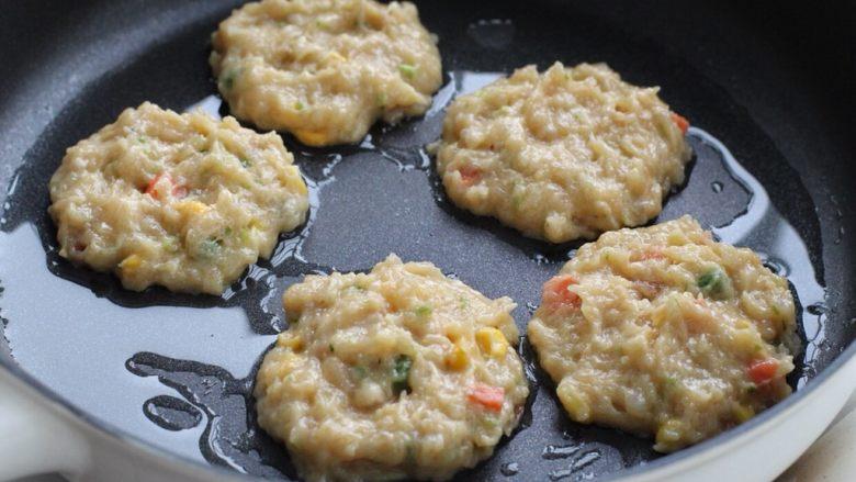 蔬菜鸡肉饼,平底不粘锅中倒适量食用油,用汤勺舀取适量肉糜放入锅中摊成饼状,形状也无需太规则。