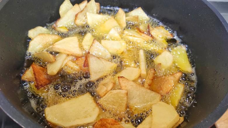 家常地三鲜,土豆放入油锅,炸熟捞出控油