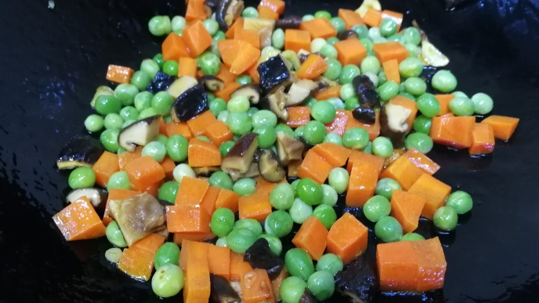 豌豆炒胡萝卜,放入香菇丁和豌豆炒匀,文火炒出香菇的香味。