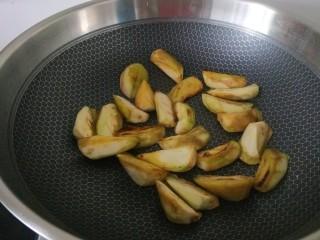 黄瓜茄子,将茄子先下入锅中中火煎至微微焦黄