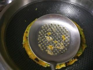 苦瓜摊鸡蛋,用漏勺把鸡蛋液均匀漏在苦瓜上。