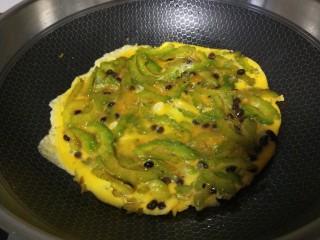 苦瓜摊鸡蛋,打开摇动锅让鸡蛋转动。
