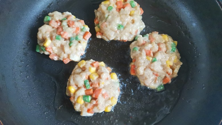 胡萝卜鸡肉饼,平底锅烧热,加入适量油,手揪一块肉馅,双手来回打成圆饼形,放入锅中小火煎