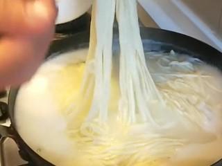 卤面条,捞入大碗,浇上卤料,撒上黄瓜丝。
