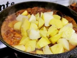 土豆炖鸡腿,鸡腿焖煮10分钟后,开盖放入土豆