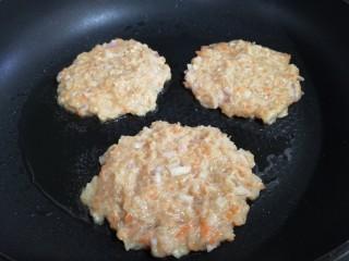 胡萝卜鸡肉饼,平底锅倒入适量油,舀入适量面糊,轻按成饼。