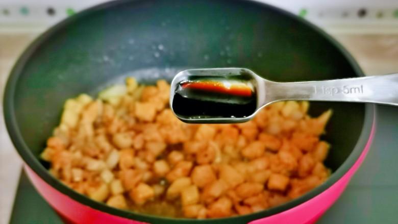 杏鲍菇炒鸡丁,再加入一勺生抽,把鸡丁炒熟。