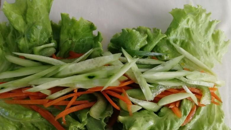 素卷三丝,把黄瓜条,胡萝卜条,青椒条铺在生菜上。