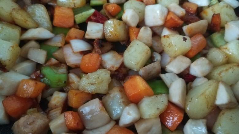 杏鲍菇炒鸡丁,最后将土豆,胡萝卜,杏鲍菇丁一起放进去进行翻炒
