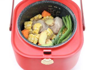 胡萝卜筒骨汤,把筒骨和胡萝卜,玉米和小葱,姜片放入电饭煲里。