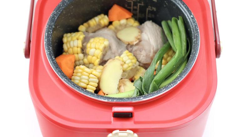 胡萝卜筒骨汤,把筒骨和胡萝卜,玉米和<a style='color:red;display:inline-block;' href='/shicai/ 157'>小葱</a>,姜片放入电饭煲里。