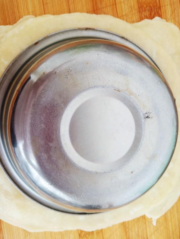 素卷三丝,蒸好的春饼上面扣一个小盆,用刀切去边缘。