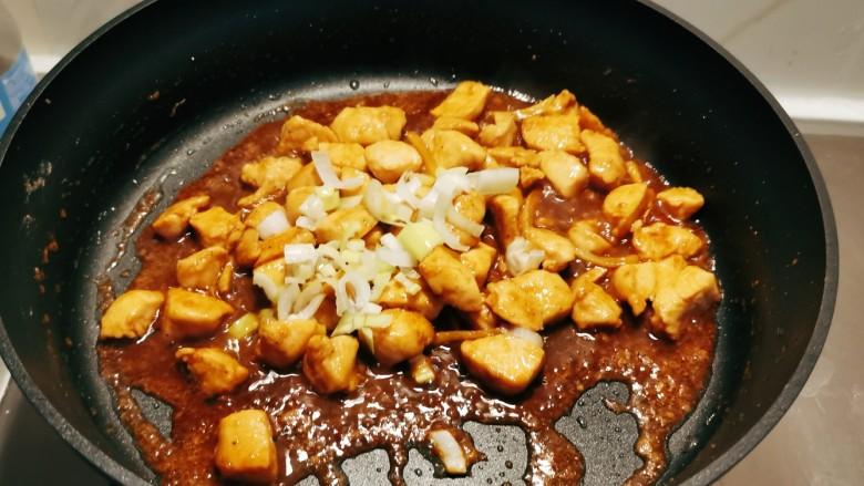 杏鲍菇炒鸡丁,放入葱片增加香味。
