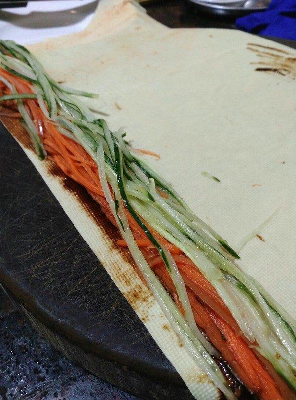 千张肉丝,放入胡萝卜丝和青瓜丝,卷成圆条状,然后斜切成小段