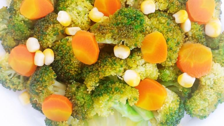 凉拌蒜蓉西兰花,将胡萝卜和玉米粒均匀的摆在树叶上当做花朵和果实。