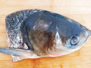 鱼头豆腐汤,一个鱼头清洗干净剁成大块。
