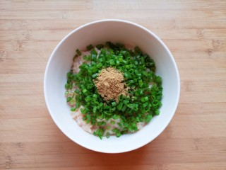 杂粮包子,将剁好的肉馅放入大碗里,放上葱花和十三香。