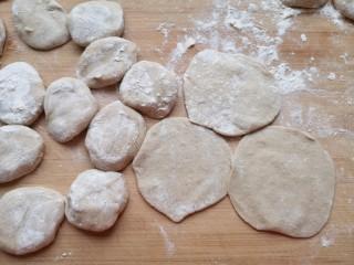 杂粮包子,将小剂子压扁,擀成中间稍厚边缘薄的包子皮。