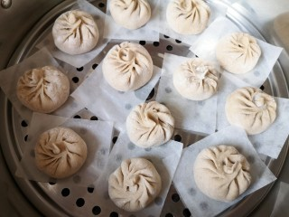 杂粮包子,蒸锅里放水放篦子,铺上油纸,放上做好的包子生坯,盖上锅盖二次发酵15分钟左右。