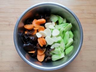 黄瓜拌木耳,将处理好的黄瓜、胡萝卜和木耳一起放入盆里,放上蒜片。
