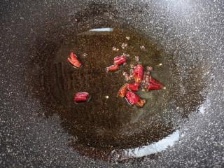 黄瓜拌木耳,炒锅内倒适量的食用油烧热,下入干红辣椒和花椒炝香。