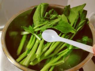 蒜蓉炒菜心,菜心择洗干净后放入开水中汆烫,水中加入2克盐和几滴食用油。