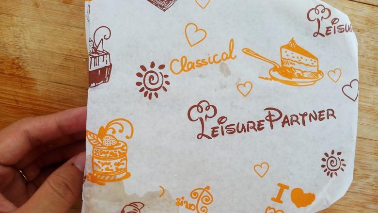 懒人必备快手早餐三明治,再放上一片吐司面包,然后用防油纸包好。