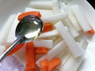 泡萝卜条,萝卜腌出水后倒掉水将白萝卜和胡萝卜放在一起加入适量米醋