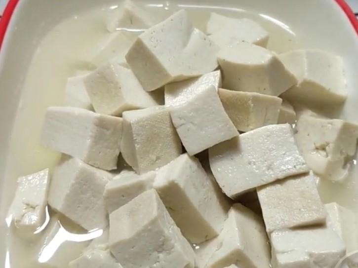 酸辣豆腐,豆腐焯完水捞入盆中。