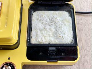 牛油果蛋清芝士火腿三明治,三明治机预热好后,刷一层油,倒入蛋白液煎至凝固,盛出。也可以直接用完整的鸡蛋。