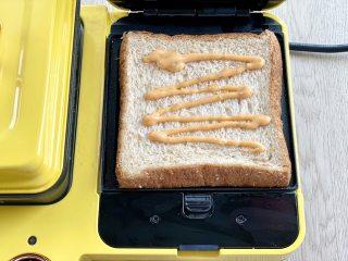 牛油果蛋清芝士火腿三明治,把吐司片放入三明治机,挤上千岛酱(或别的你喜欢的酱料)
