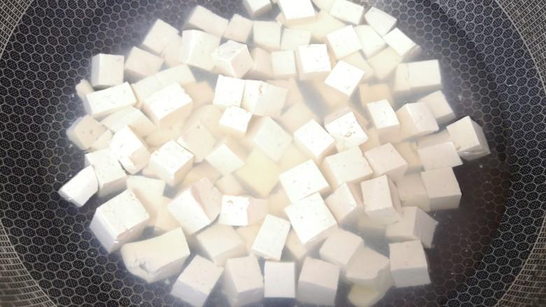 酸辣豆腐,豆腐块凉水入锅,加点盐烧开焯水,然后捞出备用。