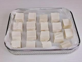 酸辣豆腐,豆腐摆在垫好油纸的烤网中。