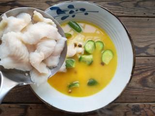 金汤鱼,将煮开的金汤一半倒入盆中,再加入剩下一半焯熟的鱼片。