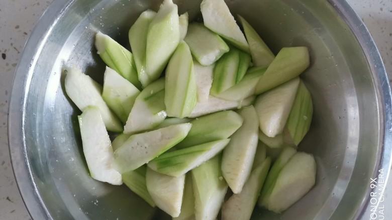 丝瓜肉片,把削皮切成滚刀块,加入适量的盐,抓拌均匀,腌制片刻