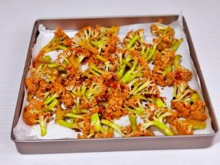 椒盐花菜,平铺垫好油纸的烤盘中。